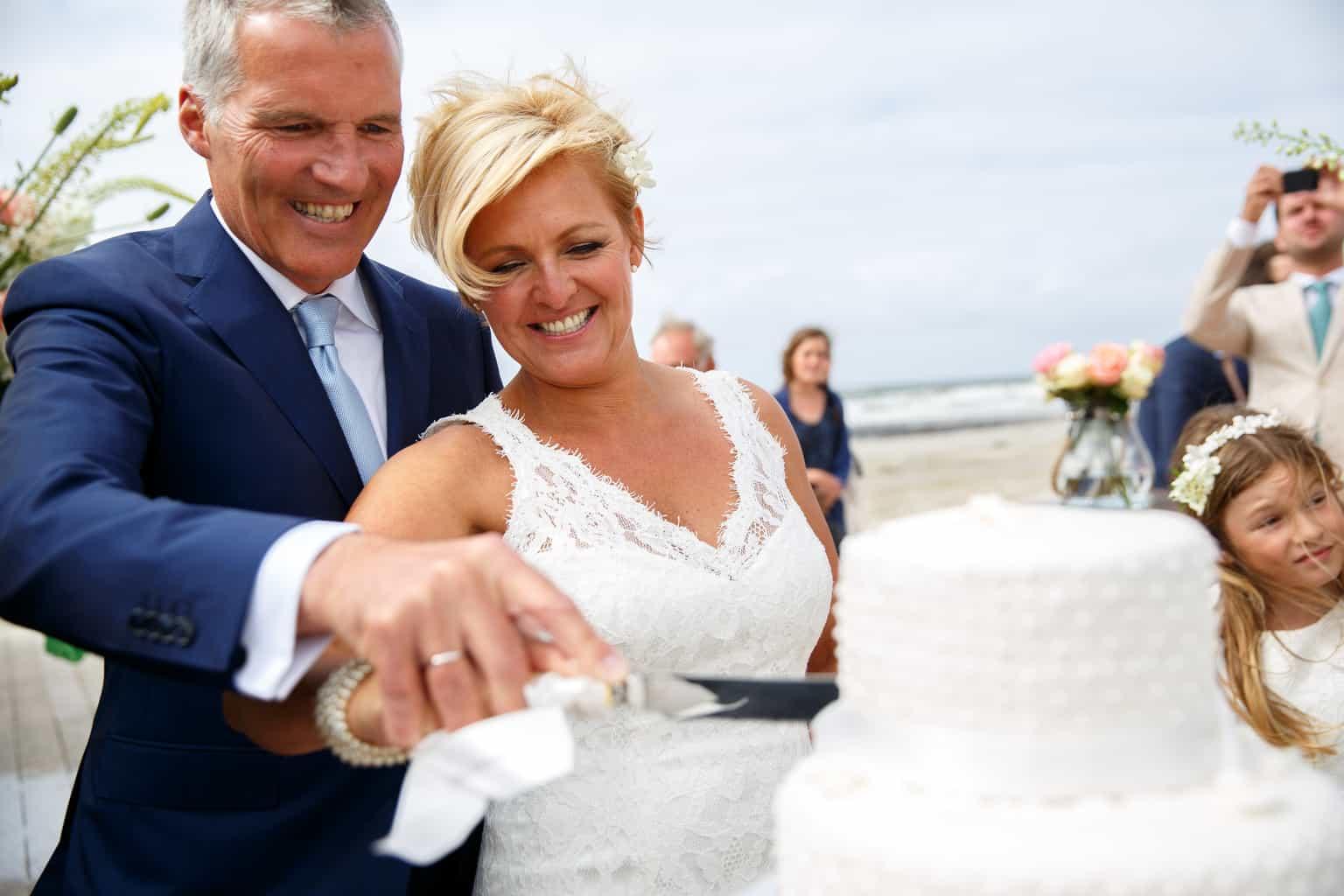 Taart aansnijden Mr, & Mrs, Huwelijk Caroline Tensen en Ernst-Jan Smids, Evert Doorn Fotografie, wedding en planning, Weddingplanner, trouwen op Vlieland, trouwen op het strand, bruidstaart Cake Affair